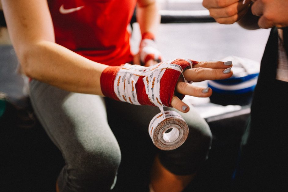 An image of a woman wrapping her hands with boxing tape.