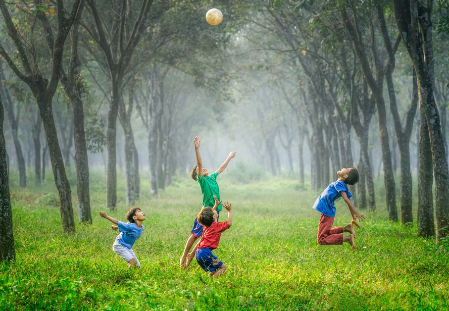 An image of children playing outside with a ball.