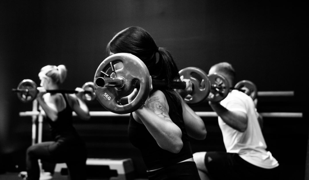 An image of three people weightlifting in a group fitness class.