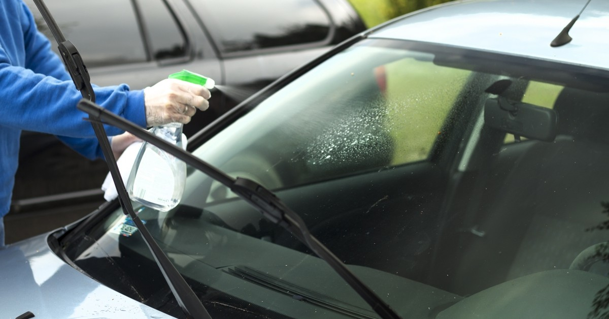 A person cleans their car window