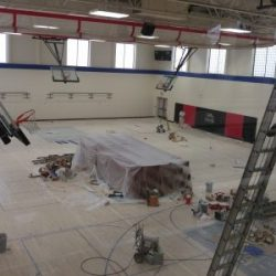 An image of an indoor basketball court with the floors covered as the walls are painted white by Painting Plus of Colorado.