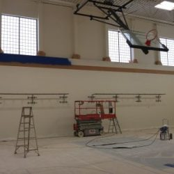An image of an indoor basketball court being painted white by Painting Plus of Colorado.