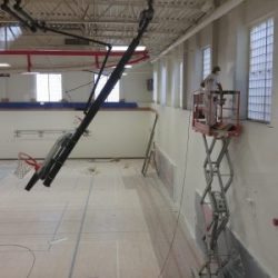 An image of an indoor basketball court whose walls are being painted by Painting Plus of Colorado.