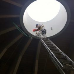 An image of a Painting Plus of Colorado worker painting an interior dome of a rec center.