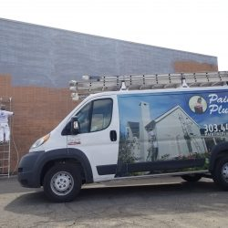 An image of the Painting Plus of Boulder van in front of a brick building being painted gray.