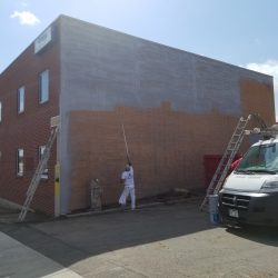 An image of the exterior of a brick building being painted gray by Painting Plus of Colorado.