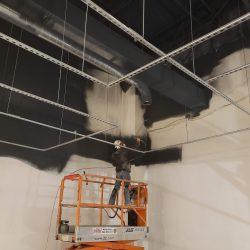 An image of the interior of a commercial building being painted black by Painting Plus of Colorado.