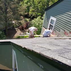 An image of the Painting Plus of Colorado on a residential roof painting the exterior siding.