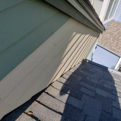 An image showing the exterior siding of a residential home that is being painted by Painting Plus of Colorado.