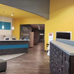 An image of the interior of a commercial fitness center that has been painting yellow, gray, and teal by Painting Plus of Colorado.