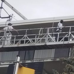 An image of the Painting Plus of Colorado team on a control lift preparing to paint the exterior of an apartment building.