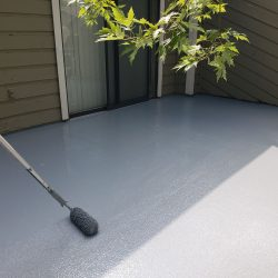 An image of a roller applying paint to the exterior surface of a patio by the Painting Plus of Colorado team.