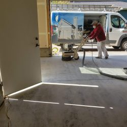 An image of a Painting Plus of Colorado contractor sanding the floors of a garage and wearing a mask to prepare for epoxy coating.