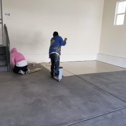An image of a Painting Plus of Colorado contractor painting then concrete floor of a garage with brown paint.