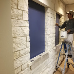 An image of a Painting Plus of Colorado contractor painting the hallway in a home's interior blue.