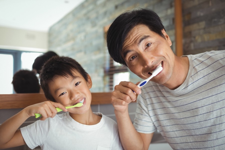 A son and father brushing their teeth