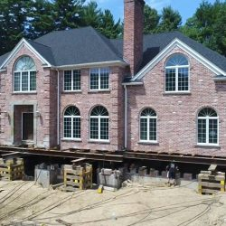 A large brick house lifted by building movers - Payne Construction Services