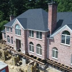Aerial view of a brick house lifted from the foundation - Payne Construction Services