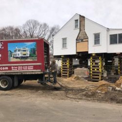 A house lifted above the ground with Payne Construction Services truck
