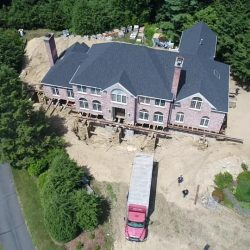 Aerial view of a house lifted at the foundation by building movers - Payne Construction Services