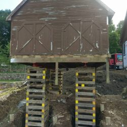 An old barn raised high above the ground with support beams - Payne Construction Services