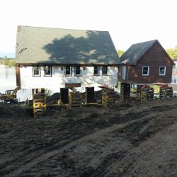 A house and barn by a lake raised above the foundation - Payne Construction Services