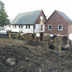 Two buildings raised above the ground for a new foundation - Payne Construction Services