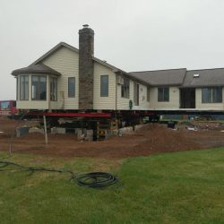 A house raised with steal beams and supported with beams for foundation repair - Payne Construction Services