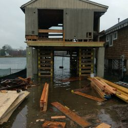 A house lifted and supported by beams during a flood - Payne Construction Services