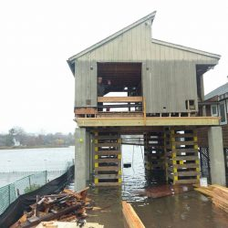 A house during a flood lifted above the ground - Payne Construction Services