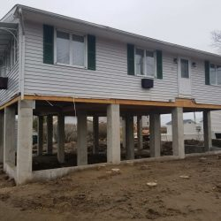 A house lifted above the ground with new concrete beam foundation - Payne Construction Services