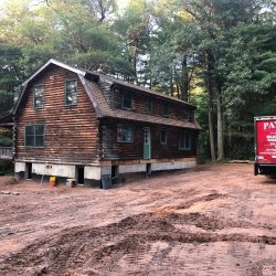 An old cabin-style house in the woods lifted at the foundation - Payne Construction Services