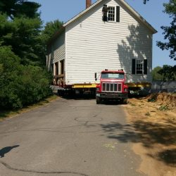 A historical house is taken on a truck down a road.