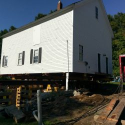 A lifted house being moved - Payne Construction Services