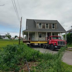 House movers carrying an old house on a truck bed - Payne Construction Services
