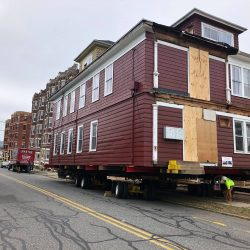 A large house lifted and sitting on a truck ready for moving - Payne Construction Services