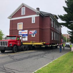 A large house being moved on a truck going down a street - Payne Construction Services