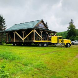 An old house sitting on a truck bed being moved - Payne Construction Services