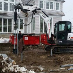 Team of contractors screwing in a helical pile in front of a house - Payne Construction Services