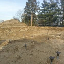 An open lot with helical piles ready for a house - Payne Construction Services
