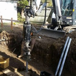 Construction work screwing in helical piles - Payne Construction Services