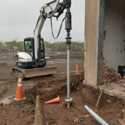 Screwing in a helical pile - Payne Construction Services