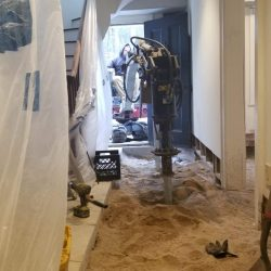A home's interior dug out so helical piles can be installed - Payne Construction Services