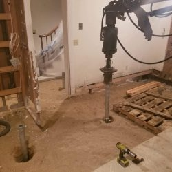 A home's floor dug out and helical piles being installed - Payne Construction Services