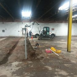 Digging channels in a commercial building for helical pile project - Payne Construction Services