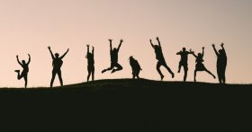 Outline of several people in a row jumping up with hands outstretched.