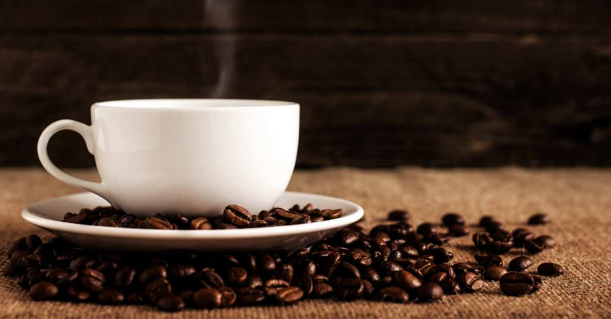 Steaming coffee mug sitting on plate surrounded by coffee beans