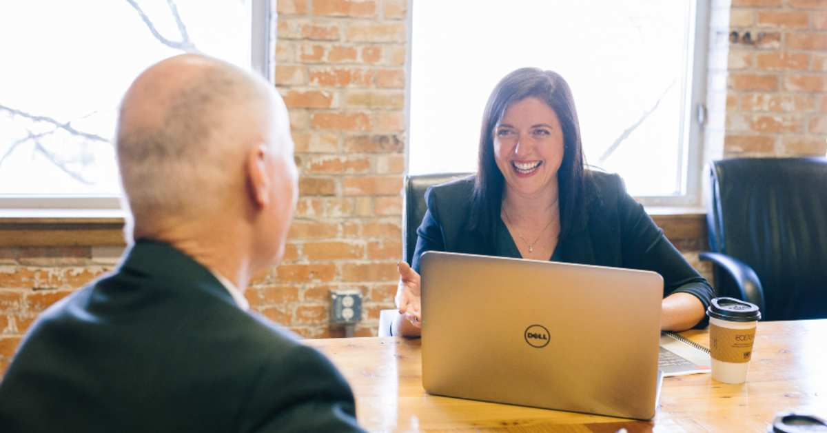 Woman smiles during meeting with man