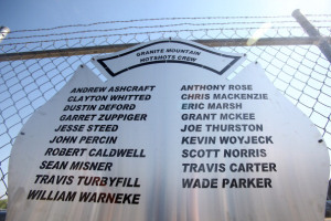A plaque engraved with names of the 19 fallen firefighters is mounted on a fence outside of Granite Mountain Hotshots Fire Station 7 in Prescott, Arizona July 2, 2013.  The Yarnell Hill fire -- which killed all but one member of a 20-strong 'hotshot' team -- was the biggest loss of firefighters' lives since the September 11 attacks, and the most from a US wildfire in 80 years. AFP PHOTO / KRISTA KENNELL        (Photo credit should read Krista Kennell/AFP/Getty Images)