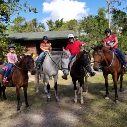 A family of four before a trail ride - Pink Flamingo Stables